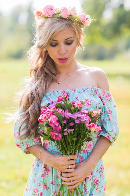 美しい金髪の女性の屋外のポートレートをクローズアップ。の花束を持つフィールドで魅力的な幸せな女の子。 Premium写真