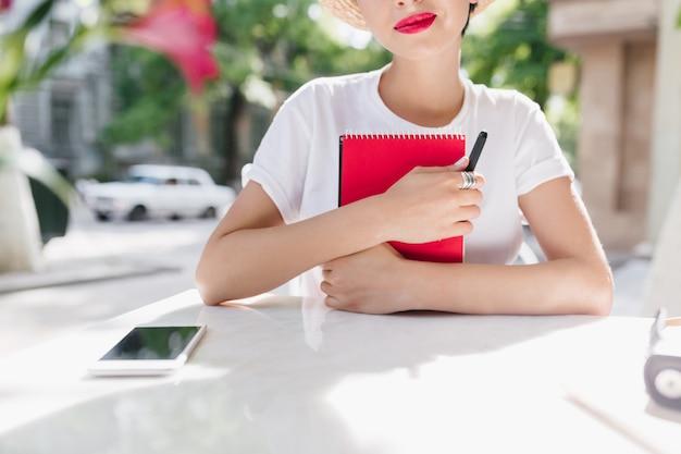 Крупным планом открытый портрет романтичной дамы в белой рубашке, держащей красный дневник и улыбающейся Бесплатные Фотографии