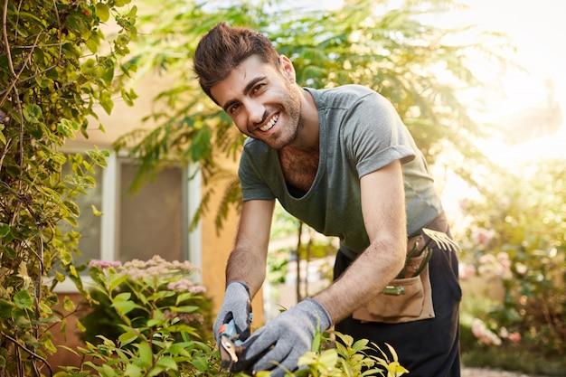 Крупным планом портрет на открытом воздухе красивого жизнерадостного бородатого кавказского фермера в синей рубашке и перчатках, улыбающегося, работающего с садовыми инструментами на своей ферме возле загородного дома Бесплатные Фотографии