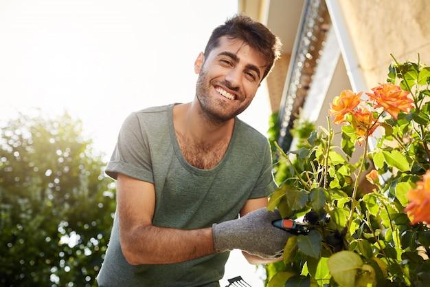 Крупным планом на открытом воздухе портрет молодого веселого бородатого мужчины в синей футболке, улыбающегося, работающего в саду с инструментами, резки листьев, полива цветов Бесплатные Фотографии