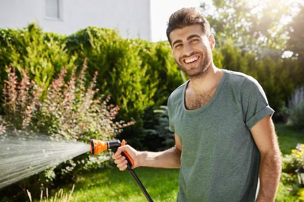 Chiuda sul ritratto all'aperto di giovani piante d'innaffiatura sorridenti del giardiniere maschio caucasico di bell'aspetto, trascorrendo l'estate in casa di campagna. Foto Gratuite