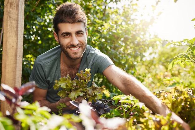 Закройте за пределами портрет молодого красивого бородатого латиноамериканца в голубой рубашке, улыбаясь в камеру, собирая листья салата в саду, поливая растения, проводя летнее утро в загородном доме. Бесплатные Фотографии