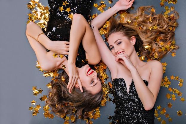Макро накладные портрет веселой молодой женщины, лежащей на звездном конфетти после вечеринки. смеющаяся европейская блондинка позирует на полу с другом во время праздника. Бесплатные Фотографии