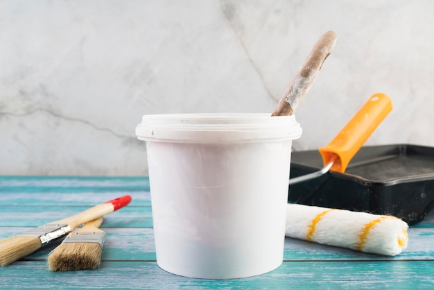 Close-up paint bucket with rollers Premium Photo