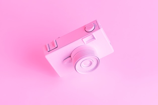 Close-up of painted old camera against pink backdrop Free Photo