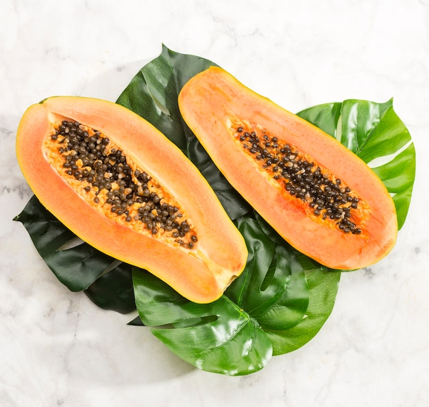 Close-up papaya on monstera leaf Free Photo