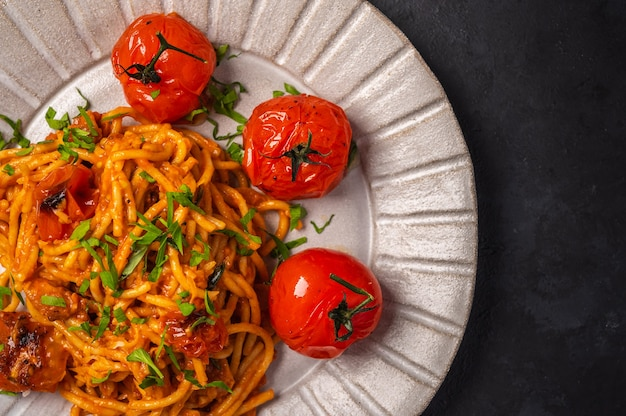 Закройте макароны с запеченными помидорами черри, сыром и петрушкой на темном текстурированном фоне Premium Фотографии