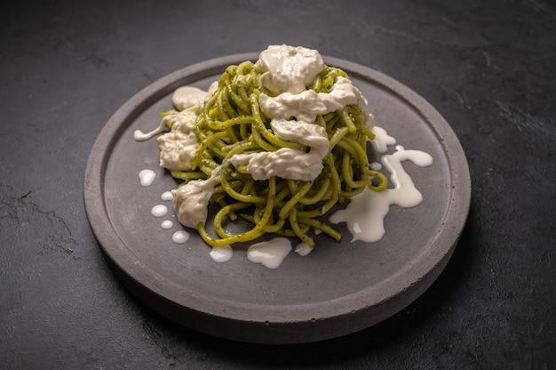 Close up pasta with pesto, stracciatella cheese served on gray ceramic plate on dark grafit background, selective focus Premium Photo
