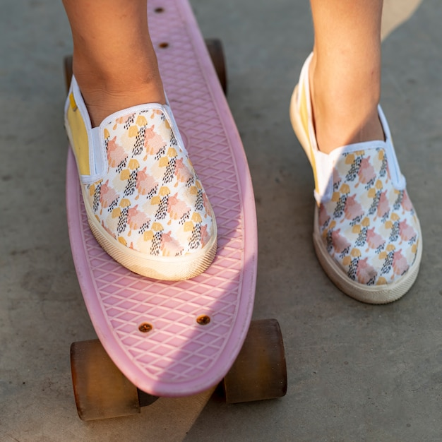 Close-up of patterned shoes and pink skateboard Free Photo