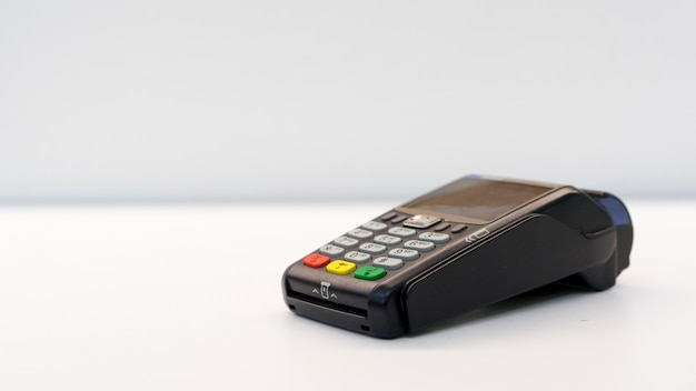Close up payment machine for paying bill by  at table Premium Photo
