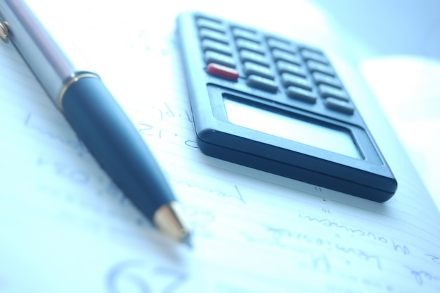 Close-up of pen with a calculator Free Photo