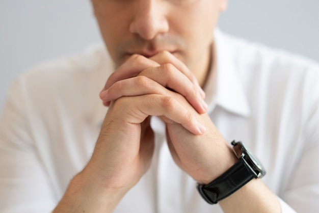 Close-up of pensive young businessman sitting with clasped hands