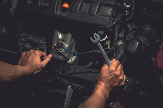 Close up, people are repair a car use hand a wrench and a screwdriver to work. Premium Photo