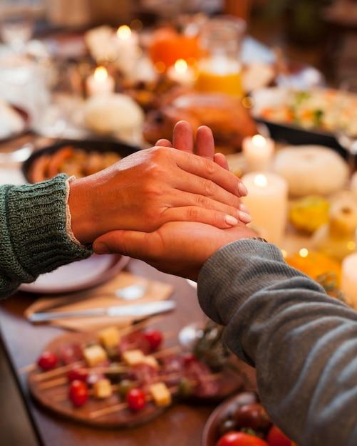 Люди крупным планом, взявшись за руки за ужином Premium Фотографии