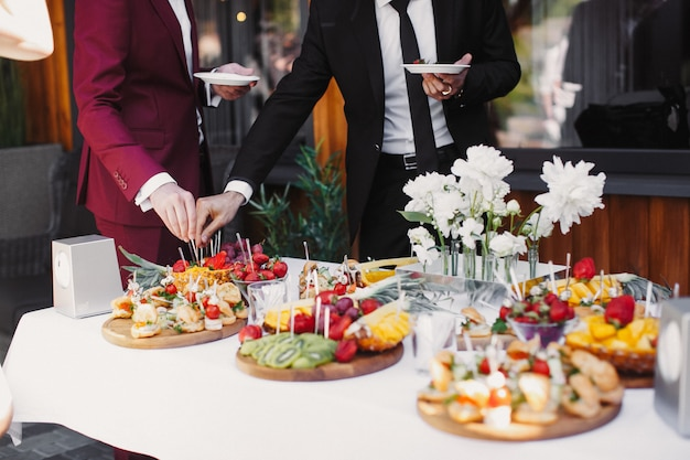 Close up of people serving themselves the fruits in buffet of restaurant Free Photo