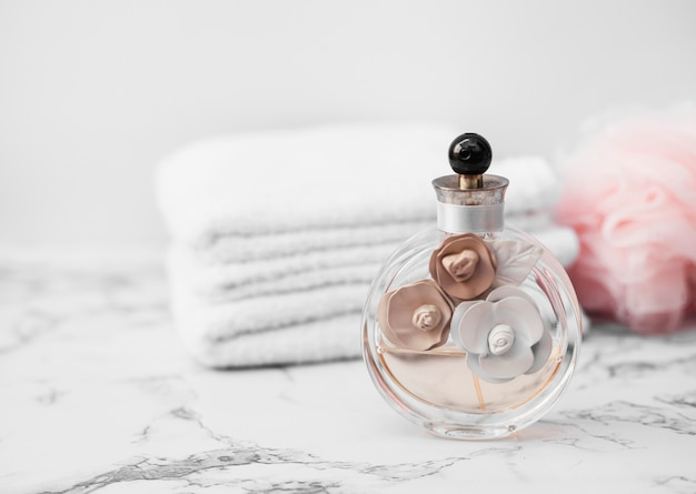 Close-up of perfume bottle in front of towel and sponge on marble surface Free Photo