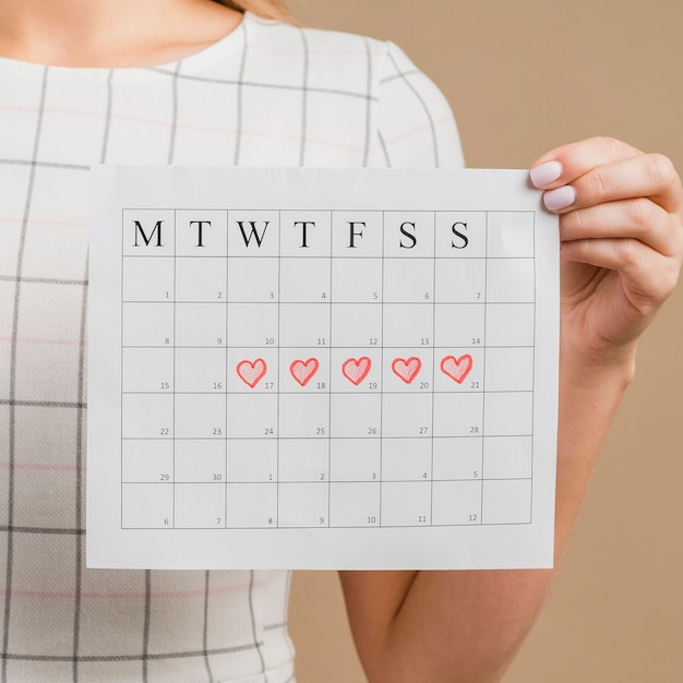 Close-up period calendar with drawn heart shapes Free Photo