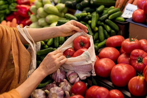 クローズアップの人がトマトを購入 Premium写真
