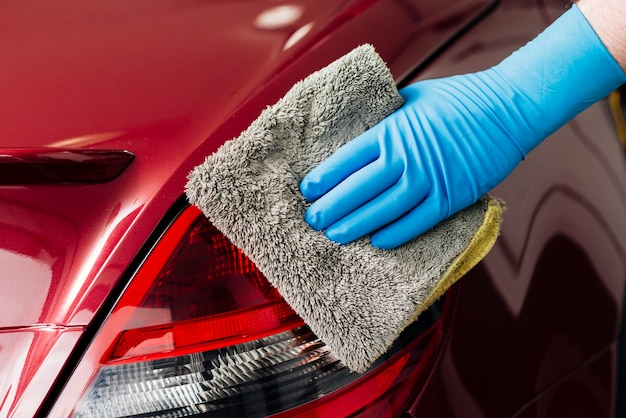 Close up of person cleaning car exterior Free Photo