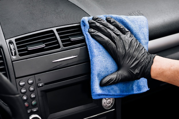 Close up of person cleaning car interior Free Photo