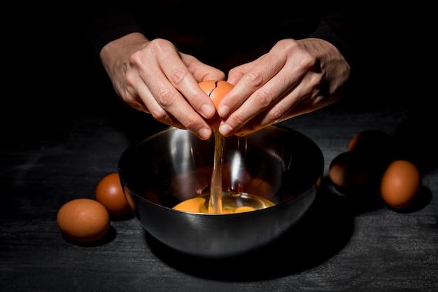 クローズアップの人が卵を割る 無料写真