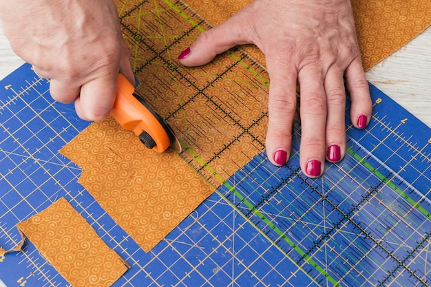 Close-up of a person cutting fabric pieces by rotary cutter on mat using ruler Free Photo
