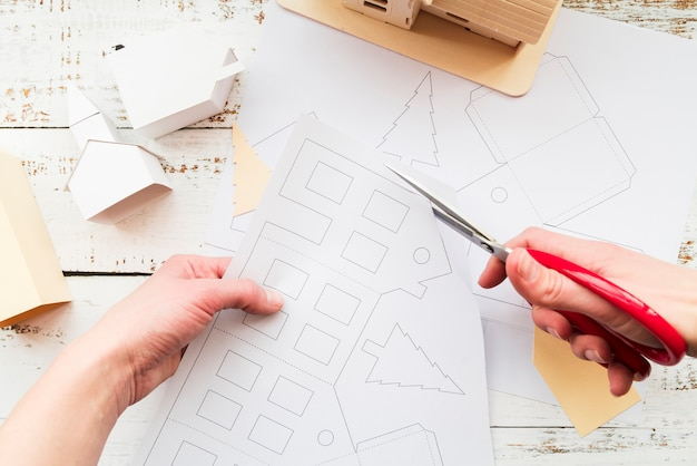 Close-up of a person cutting the house drawing with scissor Free Photo