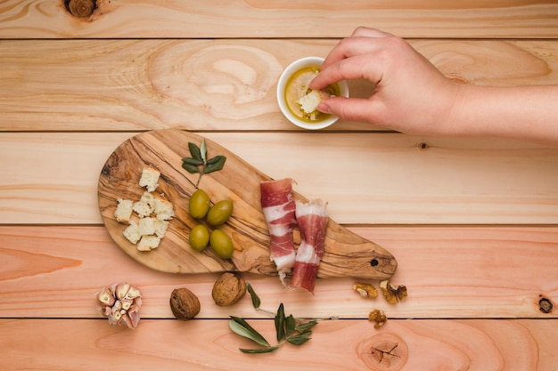 Close-up of a person dipping the bread slice in infused olive with bacon; olive and walnuts on wooden desk Free Photo