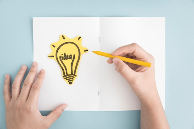 Close-up of person drawing light bulb on white page over the gray background Free Photo