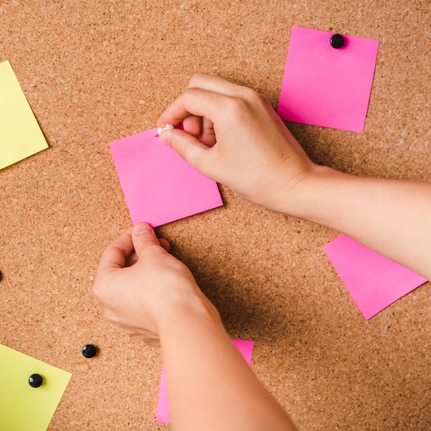 Close-up of a person fixing pink adhesive note with thumbtack on corkboard Free Photo