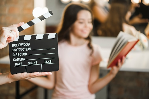 Close-up of a person holding clapper board in front of girl rehearsing Free Photo