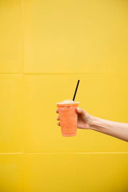 Close-up person holding glass of juice Free Photo