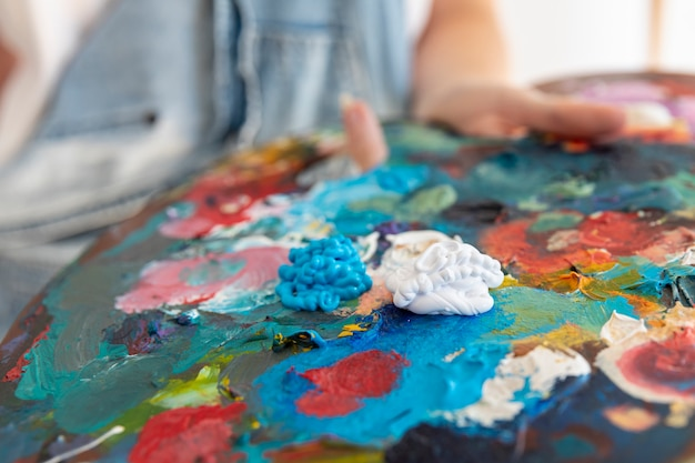 Close-up person holding painting palette Free Photo
