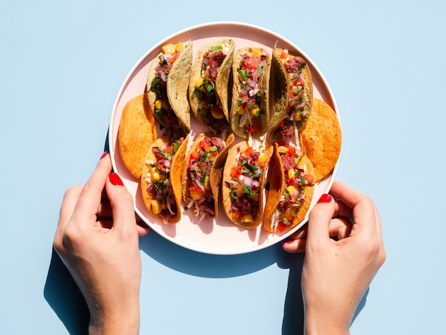 Close-up person holding plate with tacos Free Photo