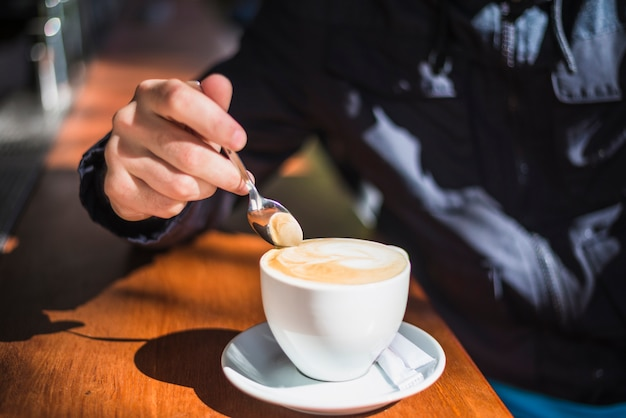 Close-up of a person holding spoon over the cappuccino or latte with frothy foam Free Photo