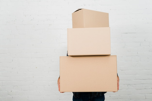 Close-up of a person holding stack of cardboard boxes against white painted wall Free Photo