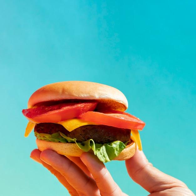 Close-up person holding up cheeseburger Free Photo