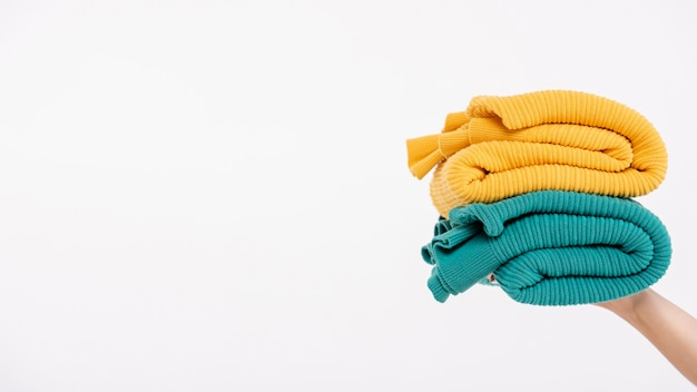 Close-up person holding up colourful sweaters Free Photo