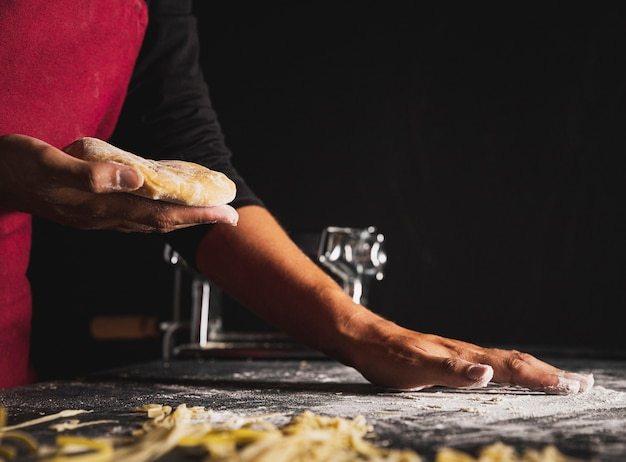 Close-up person holding up dough Free Photo