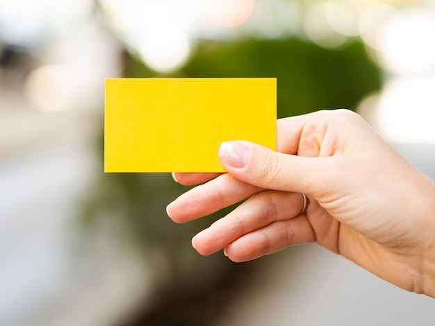 Close-up person holding up yellow card Free Photo