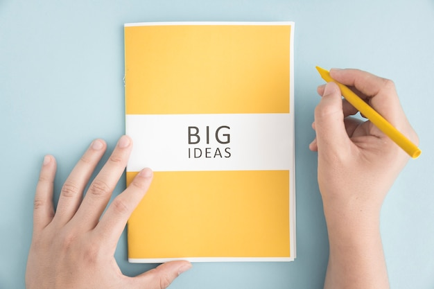 Close-up of a person holding yellow crayon with big idea book on blue background Free Photo