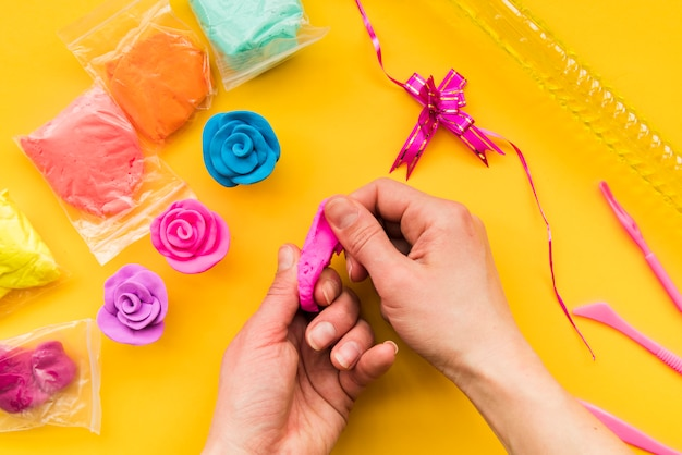 Close-up of a person making colorful clay rose on yellow backdrop Free Photo