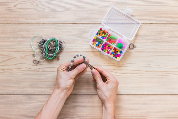 Close-up of a person making handmade bracelet with tweezers Free Photo