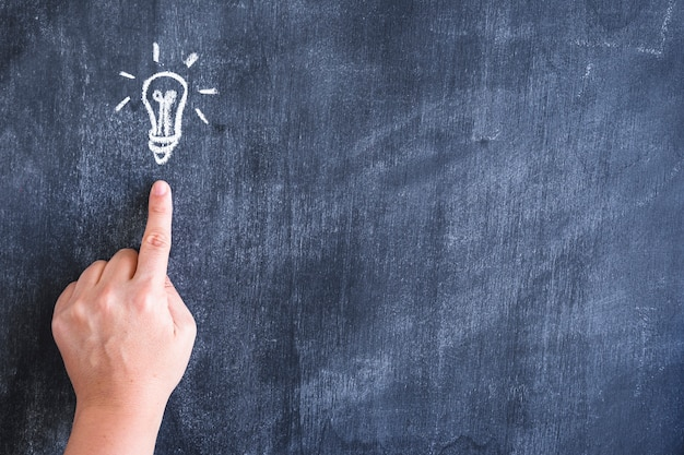 Close-up of person pointing finger on drawn light bulb with chalk over blackboard Free Photo