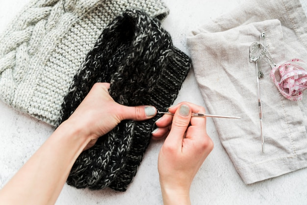 Close-up of a person's hand crocheting with wool Free Photo