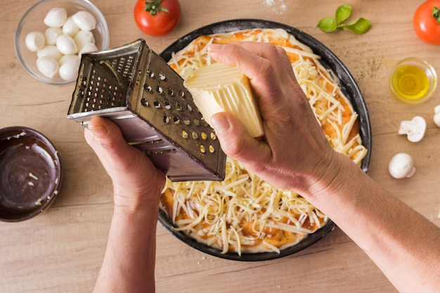 Close-up of a person's hand grating cheese over the uncooked pizza with ingredients on wooden desk Free Photo