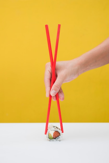 Close-up of a person's hand holding sushi rolls with red chopsticks on table against yellow backdrop Free Photo