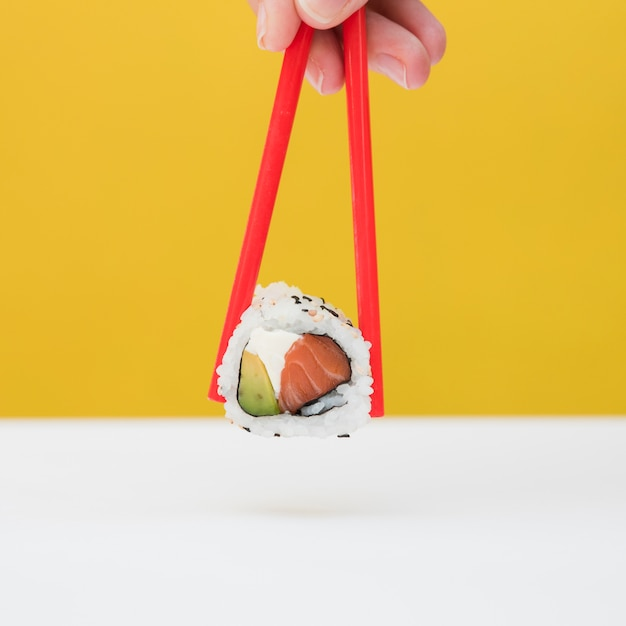 Close-up of a person's hand holding sushi with red chopsticks against yellow backdrop Free Photo