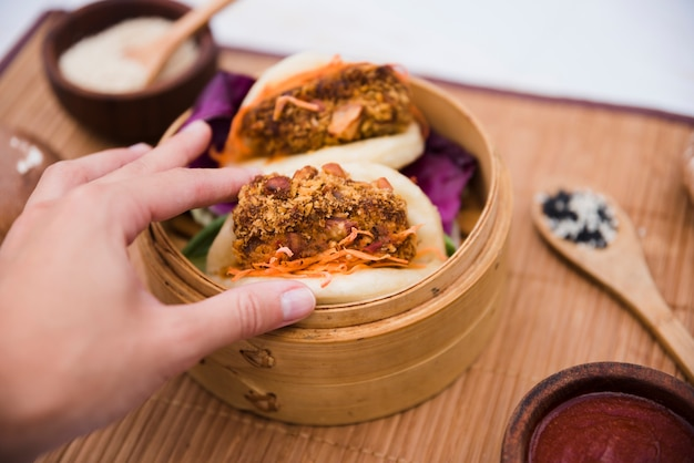 Close-up of a person's hand holding taiwan's traditional food gua bao in steamer Free Photo