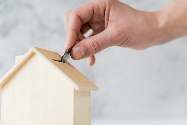 Close-up of person's hand inserting the coin in the wooden house piggybank Free Photo